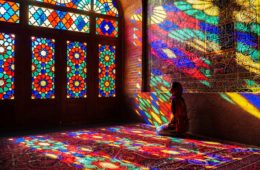 Fe sitting in prayer position while the colourful lights of the Pink Mosque reflect upon her