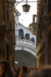 An alley with people and the Rialto Bridge in the end