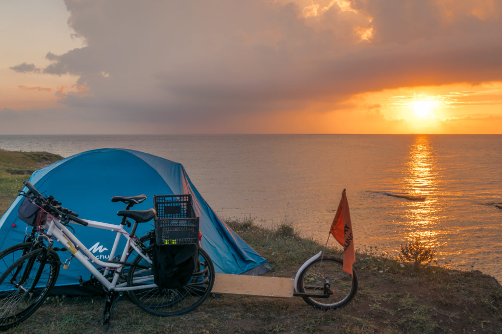 Bikes, tent and sunset seen from a cliff in Puglia