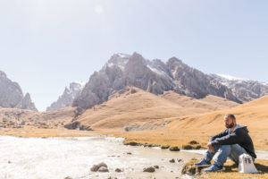 Tiago resting by the lake in Kyrgyzstan surrounded by mountains