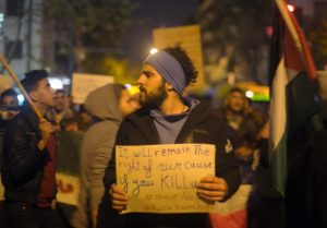 Syrian refugee holding a poster amid protests