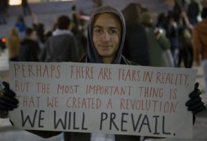 """Young Syrian refugee hold a poster saying """"Perhaps there are tears in reality, but the most important thing is that we created a revolution. We will prevail""""."""