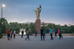 Statue to the Martyrs of the Revolution and people playing volleyball in Bishkek