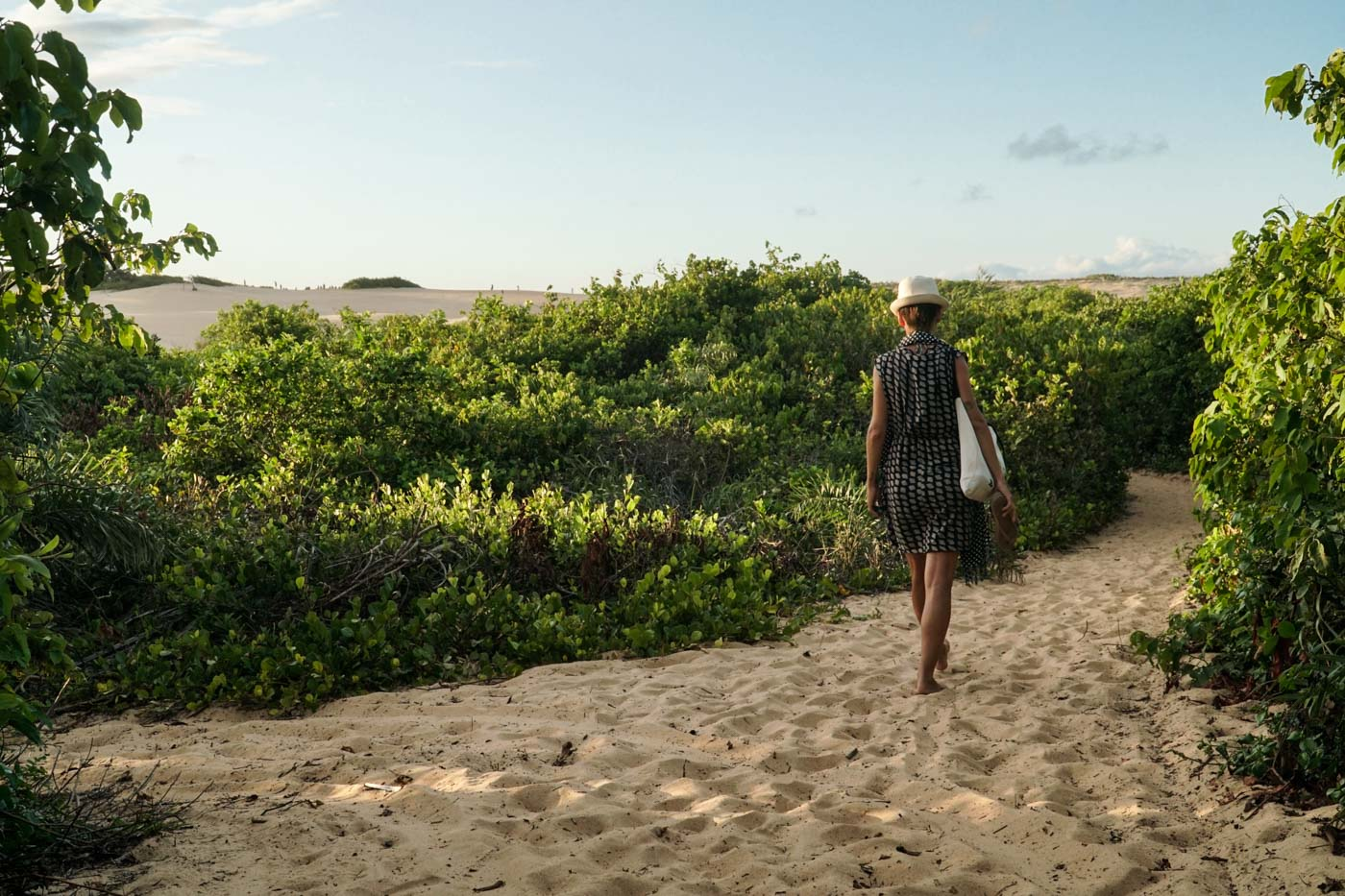 Fe walking in the sand surrounded by vegetation