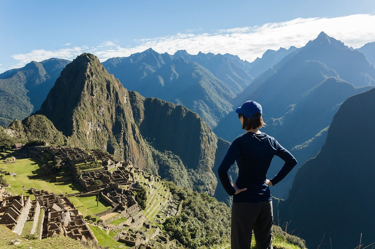 Woman looking to Macchu Picchu from above with the mountains in the background