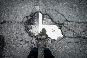 air plane reflected in a pond in the streets