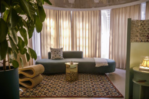 the room of Hanna Boutique Hotel showing a sofa and a modern seat in the room with closed curtains and a tall vase